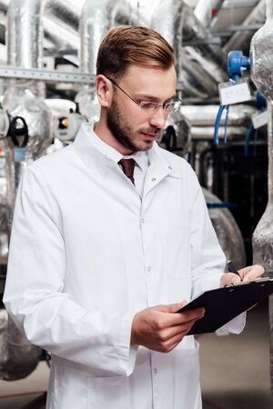 bearded engineer in white coat holding pen near clipboard and air compressed system Archivio Fotografico