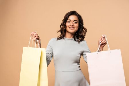 pregnant woman in grey dress smiling and holding shopping bags on beige background