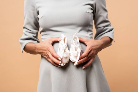 cropped view of pregnant woman in grey dress holding shoes on beige background