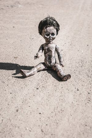 shadow near rusty and scary baby doll on ground, post apocalyptic concept