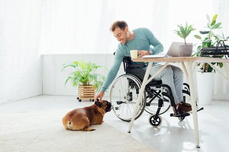 Smiling disabled man holding cup and reaching out hand to french bulldog
