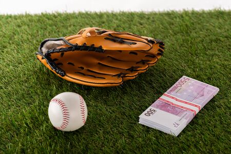 baseball glove and ball near euro banknotes on green grass isolated on white, sports betting concept Banque d'images