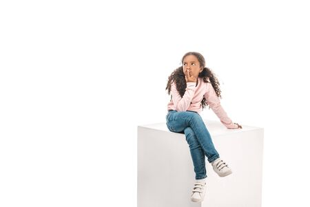 thoughtful african american child looking away while sitting on white cube isolated on white