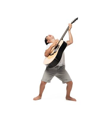 excited boy playing guitar and singing on white background Archivio Fotografico