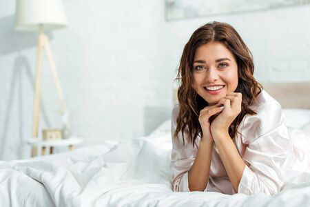 smiling woman lying in bed and looking at camera at morning