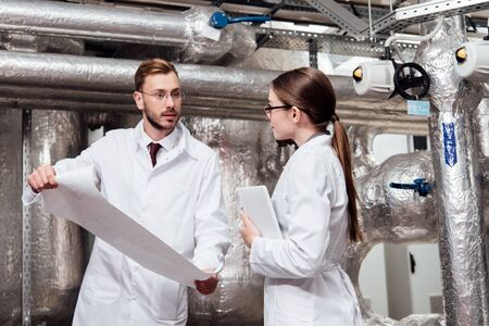 engineer in white coat looking at coworker in glasses while holding blueprint