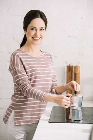 young, cheerful woman looking at camera while preparing coffee in geyser coffee maker 스톡 콘텐츠