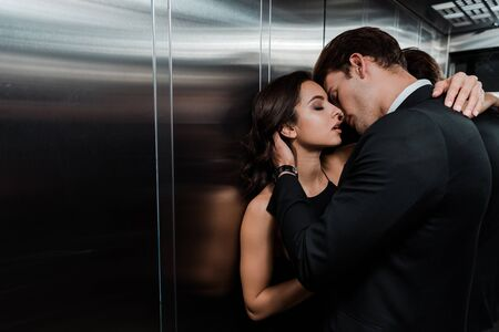 beautiful passionate couple hugging and going to kiss in lift Фото со стока
