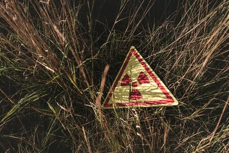top view of triangle with warning toxic symbol on grass, post apocalyptic concept