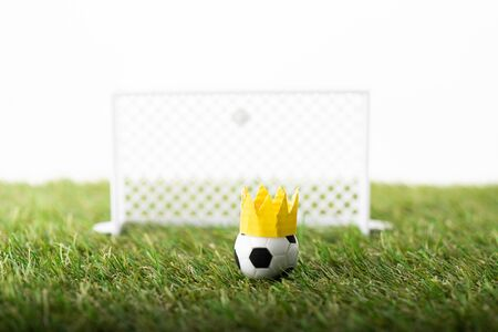 selective focus of toy football gates and ball with paper crown on green grass isolated on white, sports betting concept Banque d'images