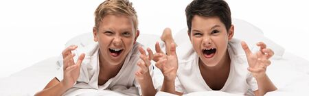 panoramic shot of two boys grimacing and showing scaring gestures while lying on bed isolated on white