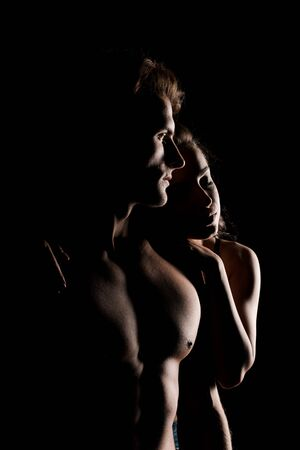 beautiful sensual couple hugging, isolated on black with backlight