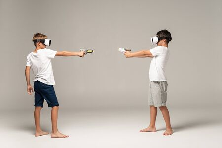 full length view of two brothers in vr headsets aiming at each other with toy guns on grey background
