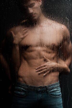 donna appassionata che abbraccia un uomo a torso nudo dietro un vetro bagnato Archivio Fotografico