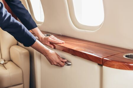 cropped view of flight attendant holding handle in private plane