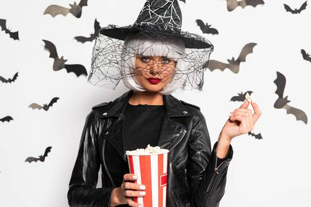 attractive woman in witch hat and wig holding popcorn in Halloween Stock Photo