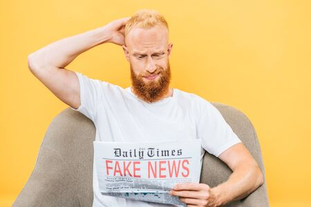thoughtful bearded man reading newspaper with fake news while sitting on armchair, isolated on yellow Stok Fotoğraf