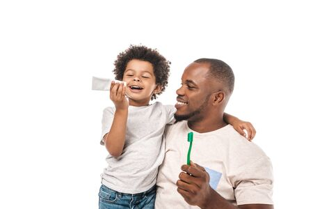 cheerful african american boy looking at toothpaste near happy father holding toothbrush isolated on white