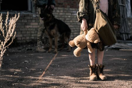 cropped view of kid holding teddy bear near man with german shepherd dog near abandoned building, post apocalyptic concept Stock Photo