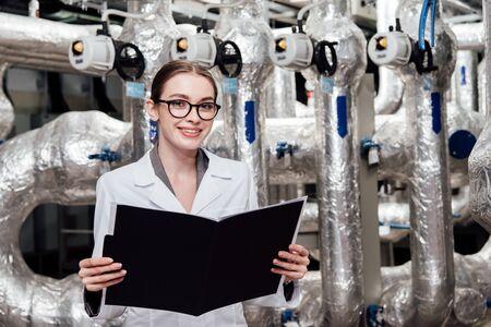 ingegnere felice e attraente in camice bianco che tiene cartella nera vicino al sistema ad aria compressa