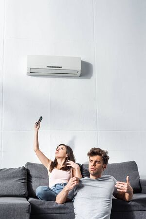 attractive girlfriend switching on air conditioner and handsome boyfriend looking away