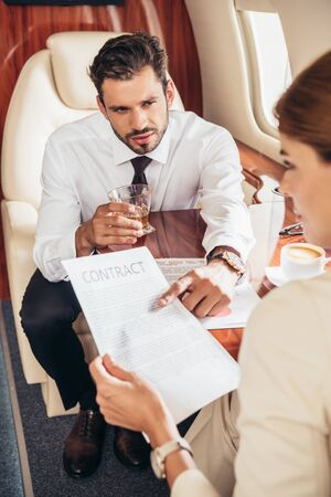 businessman pointing with finger at contract and talking with businesswoman in private plane Zdjęcie Seryjne