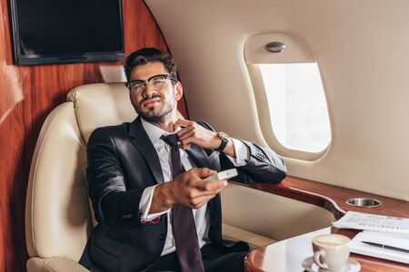 handsome businessman in suit holding remote controller in private plane