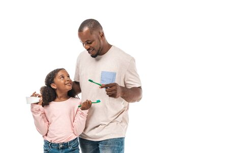 cheerful african american child holding toothbrush and toothpaste looking at father with toothbrush isolated on white 版權商用圖片
