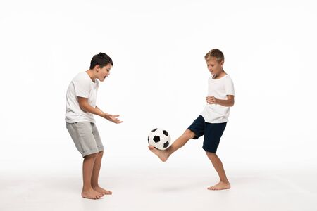 excited boy showing wow gesture while looking at brother playing with soccer ball on white background