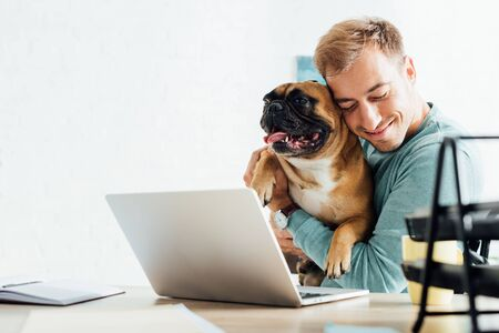 Smiling man hugging french bulldog while working on laptop
