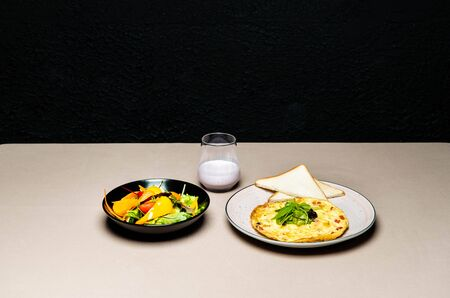 tasty salad, omelet, toasts and yogurt in glass on table