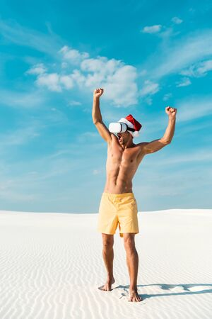 sexy man in santa hat with virtual reality headset showing yes gesture on beach in Maldives Standard-Bild