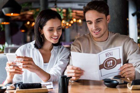 mujer feliz sosteniendo teléfono inteligente cerca del hombre con menú Foto de archivo