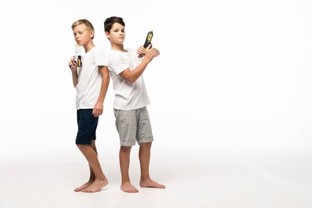two brothers standing back to back, holding toy guns and looking at camera on white background Foto de archivo