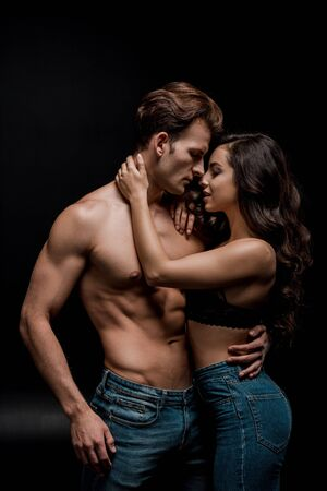 hermosa pareja seductora abrazándose, aislado en negro Foto de archivo