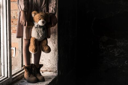 cropped view of child holding dirty teddy bear while standing on windowsill, post apocalyptic concept
