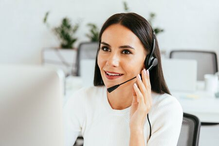 selective focus of attractive broker touching headset while working in call center
