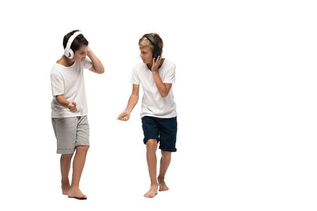 two brothers listening music in headphones and dancing on white background