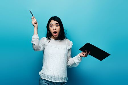excited asian journalist in white blouse holding clipboard on blue background Banco de Imagens