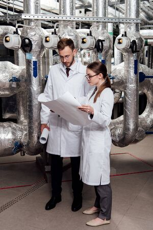 engineers in glasses and white coats looking at blueprint near air compressor system