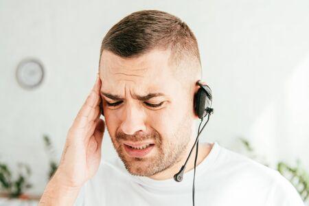 Corredor cansado y molesto tocando la cabeza mientras trabaja en el centro de llamadas