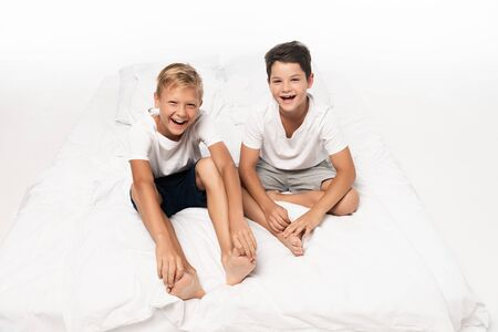 two happy brothers sitting on bed and smiling at camera on white background