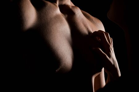 cropped view of seductive couple hugging together, isolated on black with backlight