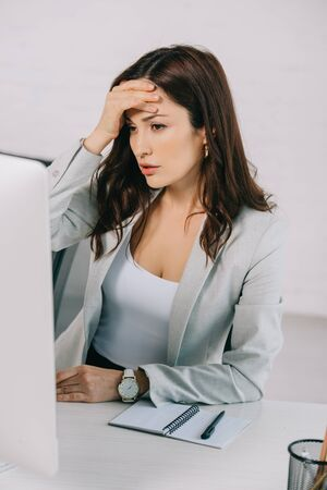 exhausted secretary holding hand near head while sitting at workplace and suffering from headache
