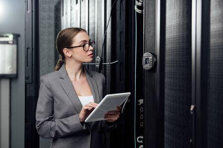 selective focus of businesswoman in glasses holding digital tablet near server racks
