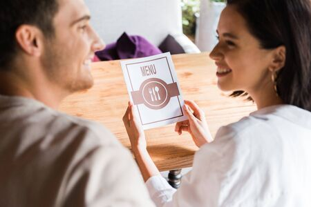 selective focus of woman holding menu and looking at man