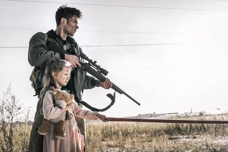 man holding gun near child with teddy bear, post apocalyptic concept Imagens