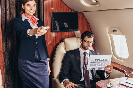 handsome businessman in suit reading newspaper and smiling flight attendant holding remote controller in private plane
