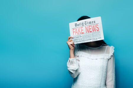 donna in camicetta bianca che tiene giornale con notizie false su sfondo blu