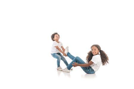joyful african american boy dragging sister by leg on white background Archivio Fotografico